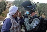 Protestors confront Israeli forces as a structure serving as a home to a Palestinian family is demolished in the southern West Bank on August 11