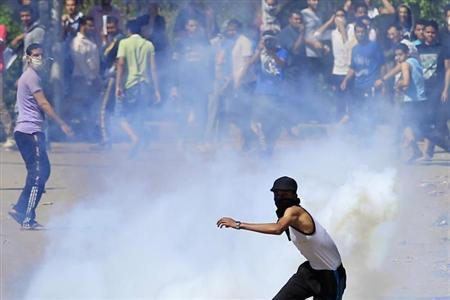 Student, supporting Muslim Brotherhood and ousted President Mursi, throws tear gas canister, earlier launched by riot police, during clashes in front of Al-Azhar University campus, in Cairo