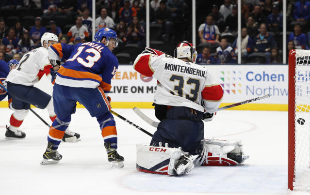 New York Islanders center Mathew Barzal (13) and Florida Panthers goaltender Sam Montembeault (33) watch as Josh Bailey's shot goes into the net during the second period of an NHL hockey game Saturday, Oct. 12, 2019, in Uniondale, N.Y. Bailey is barely visible at upper left. (AP Photo/Kathy Willens)