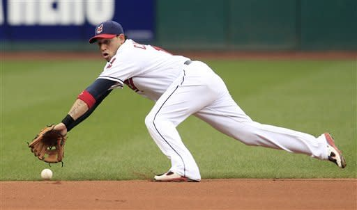 Cleveland Indians' Asdrubal Cabrera fields a ball hit by Texas Rangers' Elvis Andrus in the first inning in a baseball game, Friday, May 4, 2012, in Cleveland. Andrus was safe at first base. (AP Photo/Tony Dejak)
