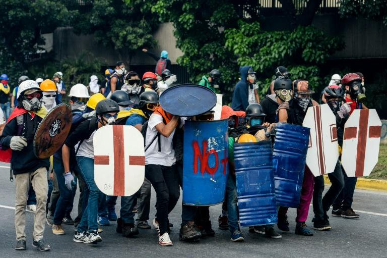 Venezuelan opposition activists protect themselves against water cannons during clashes with police, in Caracas, on May 1, 2017