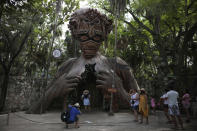 """Tourists wait their turn to pose for a photo with a figurative sculpture that serves as an archway by South African artist Daniel Popper titled, """"Ven a la Luz"""" at the Ahau Tulum resort, Quintana Roo state, Mexico, Monday, Jan. 4, 2021. Concern is spreading that the winter holiday bump in tourism could be fleeting because it came as COVID-19 infections in both Mexico and the United States were reaching new heights. (AP Photo/Emilio Espejel)"""