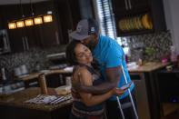 """Freddie De Los Santos kisses his wife, Jeanette, at their home in Hopewell Junction, N.Y., on Wednesday, Aug. 19, 2021. """"I function pretty well right now, but it hasn't been easy,"""" he says. He credits psychotherapy, along with a deep Christian faith, a very patient family, a love for painting, and cycling. (AP Photo/Emilio Morenatti)"""