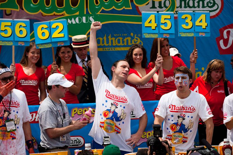 Four-time reigning champion Joey Chestnut, center, raises his arm in victory as he wins his fifth Nathan's Famous Hot Dog Eating World Championship with a total of 62 hot dogs and buns, Monday, July 4, 2011, at Coney Island, in the Brooklyn borough of New York.  (AP Photo/John Minchillo)