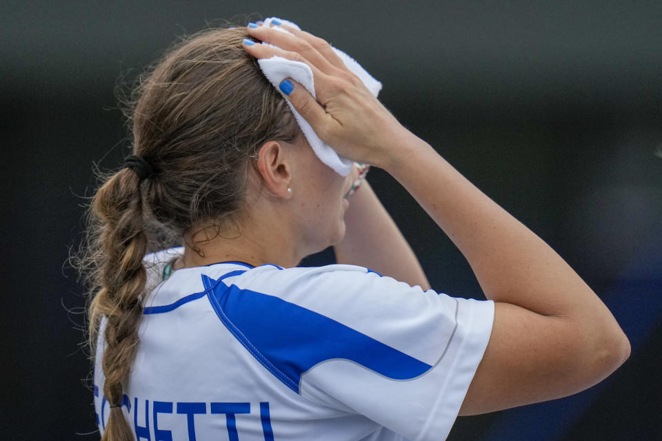 Italy's Greta Cecchetti wipes the sweat from her face during the softball game between the Italy and Australia at the 2020 Summer Olympics, Thursday, July 22, 2021, in Fukushima , Japan. (AP Photo/Jae C. Hong)
