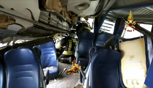 <p>This image provided by the Italian firefighters Vigili del Fuoco shows firefighters inside a train wagon trying to help a passenger out after the train derailed at the station of Pioltello Limito, on the outskirts of Milan, Italy, Thursday, Jan. 25, 2018. (Photo: Italian Firefighters Vigili del Fuoco via AP) </p>