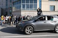 """<p>Cars drove through the area, including one from which a fan with a Ruff Ryders sweatshirt rose from the sun roof and threw up an """"X"""" to show support for the beloved rapper.</p>"""