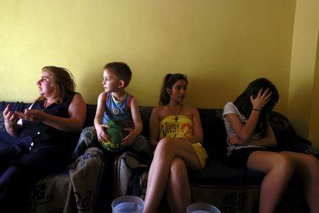 Anthoula Papazoi (L) reacts as she sits beside her son Anastasis (2nd L), 5, and daughters Elli (2nd R), 16, and Nikoleta, 13, at their home in the city of Ioannina, Greece July 10, 2015. Picture taken July 10, 2015.   REUTERS/Cathal McNaughton