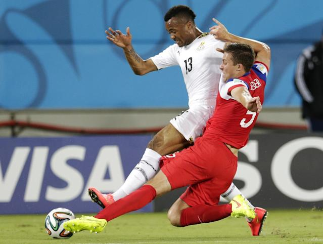 United States' Matt Besler, right, slides under Ghana's Jordan Ayew to take the ball away during the group G World Cup soccer match between Ghana and the United States at the Arena das Dunas in Natal, Brazil, Monday, June 16, 2014. (AP Photo/Petr David Josek)