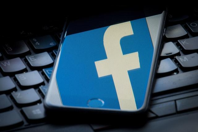 The Facebook logo reflected on the screen of a smartphone resting on a laptop keyboard