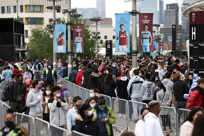 People queue outside a mass vaccination centre for those aged 18 and over at the London Stadium, amid the coronavirus pandemic, in east London, Britain, June 19, 2021. REUTERS/Henry Nicholls