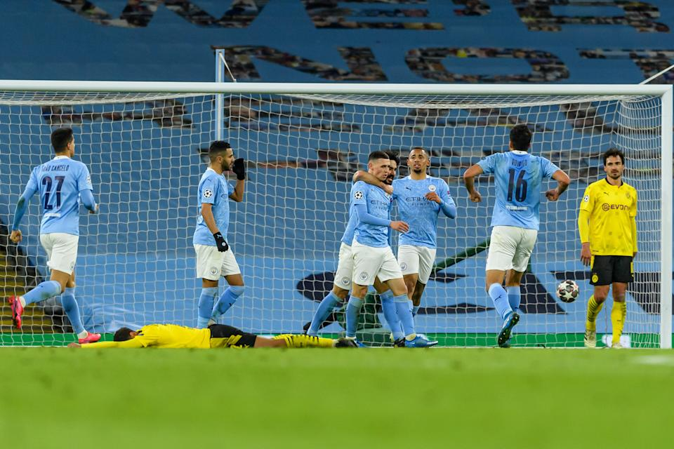 MANCHESTER, ENGLAND - APRIL 06: (BILD ZEITUNG OUT) Phil Foden of Manchester City celebrates after scoring his team's second goal with teammates during the UEFA Champions League Quarter Final match between Manchester City and Borussia Dortmund at Manchester City Football Academy on April 6, 2021 in Manchester, United Kingdom. Sporting stadiums around the UK remain under strict restrictions due to the Coronavirus Pandemic as Government social distancing laws prohibit fans inside venues resulting in games being played behind closed doors. (Photo by Vincent Mignott/DeFodi Images via Getty Images)