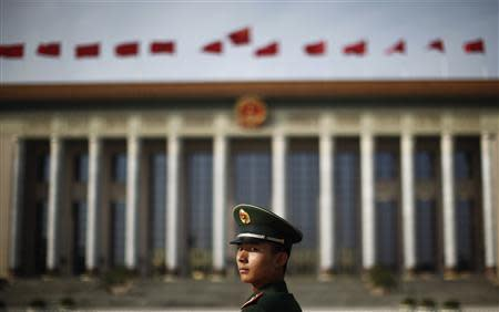 A paramilitary police officer stands in front of the Great Hall of the People at Beijing's Tiananmen Square, in this file picture taken November 7, 2012. REUTERS/Carlos Barria