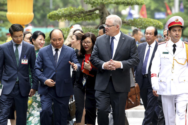 Australian Prime Minister Scott Morrison, center, talks with his Vietnamese counterpart Nguyen Xuan Phuc, second from left, while walking at the Presidential Palace in Hanoi, Vietnam, Friday, Aug. 23, 2019. Morrison is on a three-day official visit to Vietnam. (AP Photo/Duc Thanh)