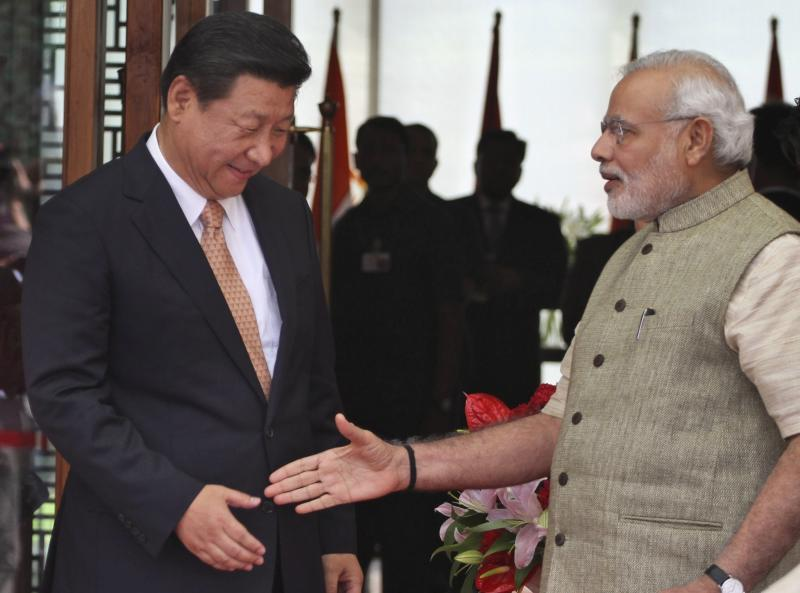 """FILE - In this Sept. 17, 2014, file photo, Indian Prime Minister Narendra Modi, right, welcomes Chinese President Xi Jinping, upon his arrival at a hotel in Ahmadabad, India. India's Ministry of External Affairs said Wednesday, Oct. 9, 2019, that Xi and Modi would meet for a second informal summit in the southern coast city of Chennai on Oct. 11 and 12 to """"exchange views on deepening"""" the two countries' development. (AP Photo/Ajit Solanki, File)"""