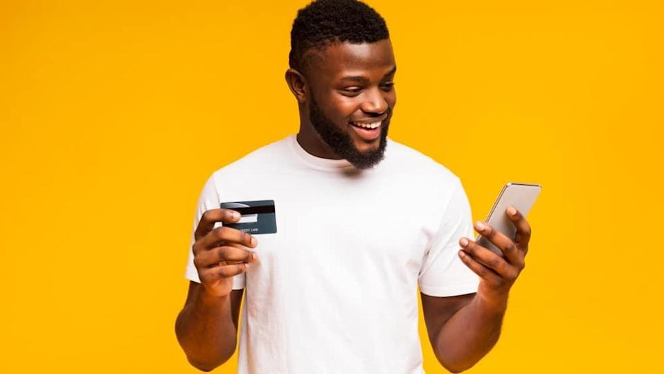 Man using credit card and smartphone for purchasing goods online.
