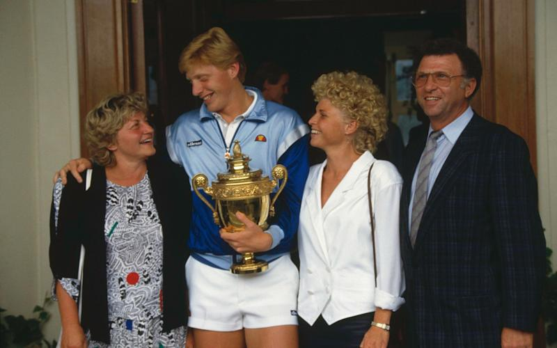Becker holding the Gentlemen's Singles Challenge Cup Trophy with his mother Elvira, sister Sabine and father Karl-Heinz in 1986 - Popperfoto