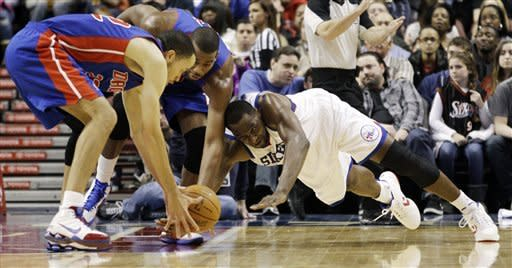 Detroit Pistons' Tayshaun Prince, left, and Greg Monroe, center, battle for a loose ball with Philadelphia 76ers' Elton Brand in the first half of an NBA basketball game, Saturday, Jan. 28, 2012, in Philadelphia. (AP Photo/Matt Slocum)