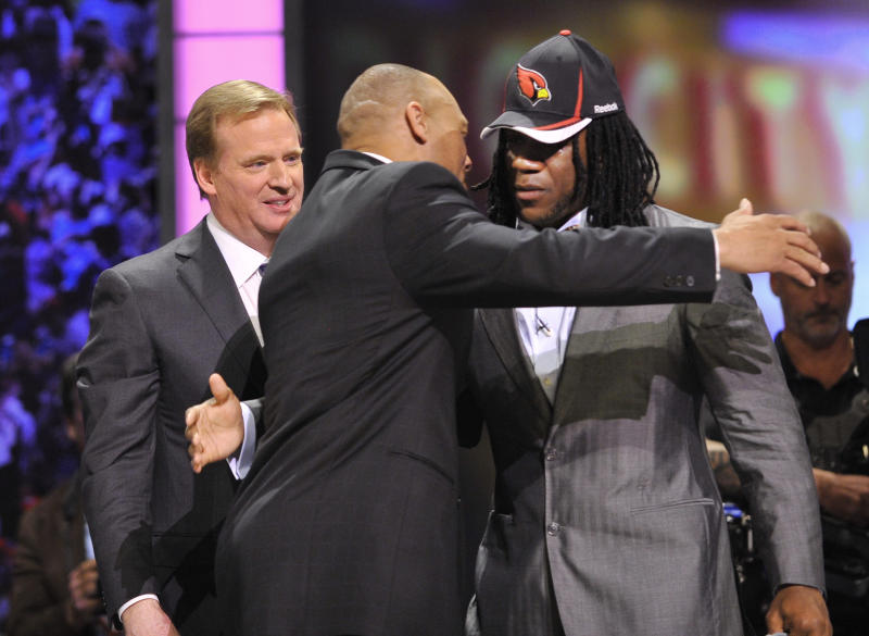 Virginia Tech running back Ryan Williams, right, hugs former defensive back Aeneas Williams as NFL Commissioner Roger Goodell, left, looks on after he was selected by the Arizona Cardinals in the second round of the NFL football draft at Radio City Music Hall ,Friday, April 29, 2011, in New York. (AP Photo/Stephen Chernin)
