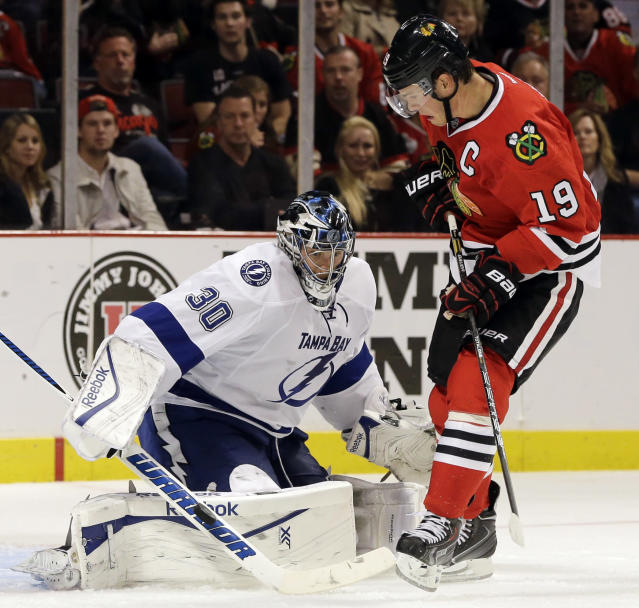 Tampa Bay Lightning goalie Ben Bishop, left, blocks a shot by Chicago Blackhawks' Jonathan Toews during the second period of an NHL hockey game in Chicago, Saturday, Oct. 5, 2013. (AP Photo/Nam Y. Huh)
