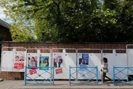 A woman walks past official European election posters in a street in Amiens
