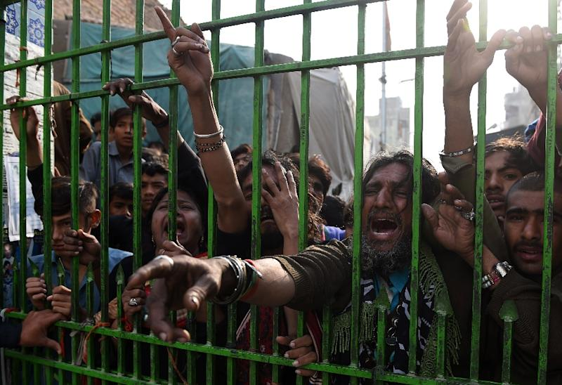 Devotees gather outside the closed gate of the shrine of 13th century Muslim Sufi saint Lal Shahbaz Qalandar, in the souther Pakistani town of Sehwan, on February 17, 2017, a day after a bomb blew up at the shrine (AFP Photo/Asif HASSAN)