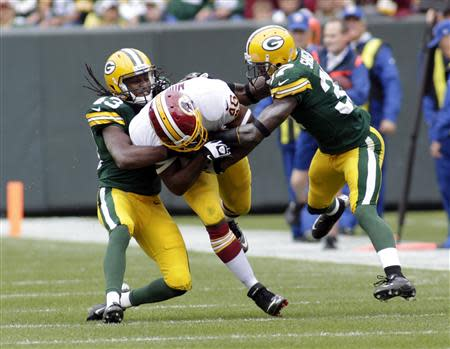 Washington Redskins running back Alfred Morris (C) is tackled by Green Bay Packers safety M.D. Jennings (L) and cornerback Sam Shields during the first half of their NFL football game in Green Bay, Wisconsin September 15, 2013. REUTERS/Darren Hauck