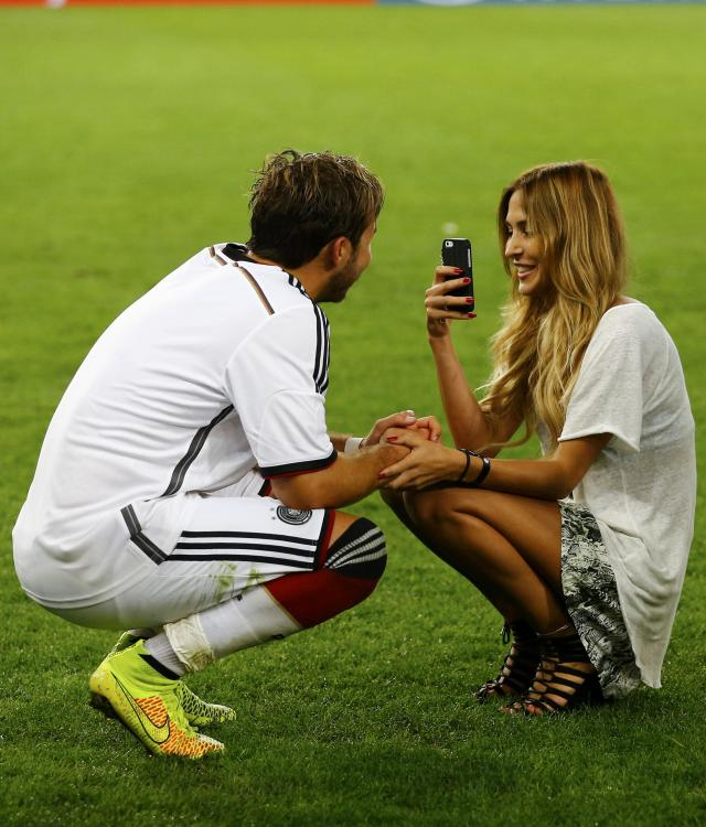 Germany's Mario Goetze (L) has his picture taken by model girlfriend Ann-Kathrin Brommel after they won their 2014 World Cup final against Argentina at the Maracana stadium in Rio de Janeiro July 13, 2014. REUTERS/Darren Staples (BRAZIL - Tags: SOCCER SPORT WORLD CUP FASHION)