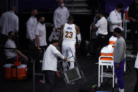 Los Angeles Lakers forward LeBron James walks to the locker room after kicking a chair following an injury during the first half of an NBA basketball game against the Atlanta Hawks Saturday, March 20, 2021, in Los Angeles. (AP Photo/Marcio Jose Sanchez)