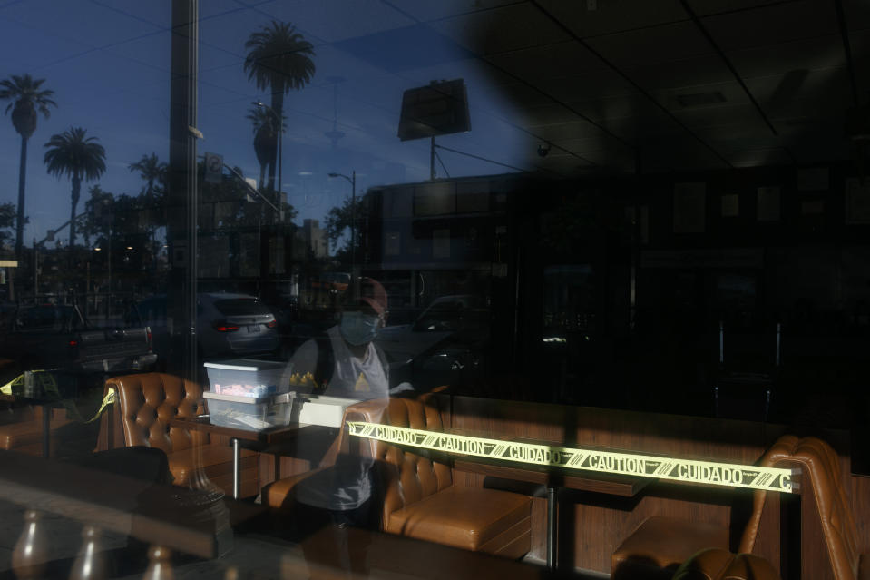 A man wearing a mask is reflected in the window of a restaurant with caution tape around its booths amid the coronavirus pandemic in the Westlake neighborhood of Los Angeles, Thursday, May 21, 2020. While most of California took another step forward to partly reopen in time for Memorial Day weekend, Los Angeles County didn't join the party because the number of coronavirus cases has grown at a pace that leaves it unable to meet even the new, relaxed state standards for allowing additional businesses and recreational activities. (AP Photo/Jae C. Hong)