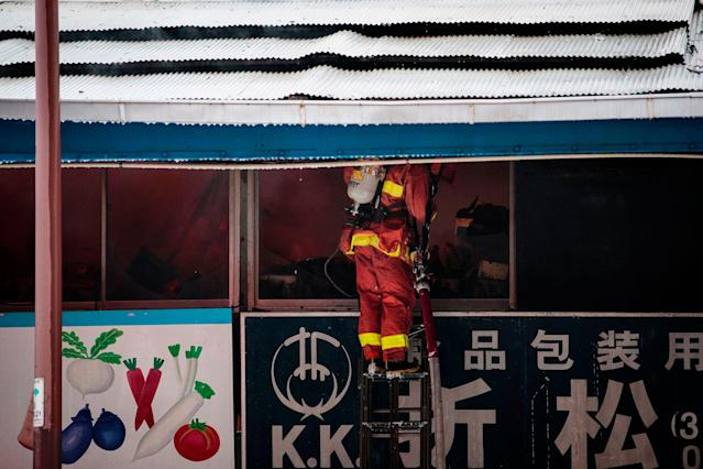 <p>A Japanese firefighter tries to extinguish a fire inside a shop at Tokyo's Tsukiji fish market on August 3, 2017. (Photo: Behrouz Mehri/AFP/Getty Images) </p>