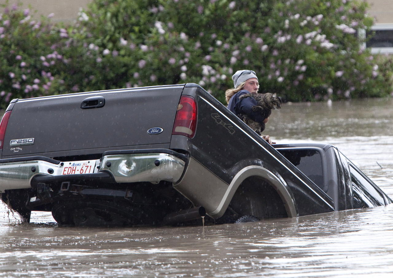 Kevan Yaets crawls out the back window of his pick up truck with his cat Momo as flood waters sweep him downstream and submerge the cab in High River, Alberta on June 20, 2013 after the Highwood River overflowed its banks. Hundreds of people have been evacuated with volunteers and emergency crews helping to aid stranded residents.