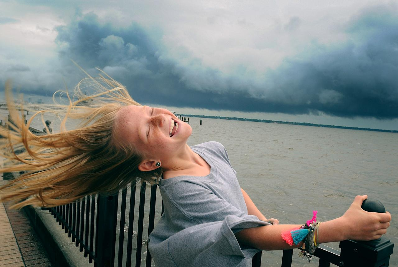 Winnie Pajcic, 9, holds on to a railing as she leans back in the wind during a visit to Stockton Park in Ortega, Fla., in the aftermath of Tropical Storm Beryl on Monday May 28, 2012. Beryl came ashore early Monday near Jacksonville Beach with near-hurricane-strength winds of 70 mph. (AP Photo/The Florida Times-Union, Kelly Jordan)