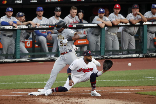 National League's Josh Bell, left, of the Pittsburgh Pirates, is safe at first for a single as American League first baseman Carlos Santana, of the Cleveland Indians, handles the throw during the second inning of the MLB baseball All-Star Game, Tuesday, July 9, 2019, in Cleveland. (AP Photo/Ron Schwane)