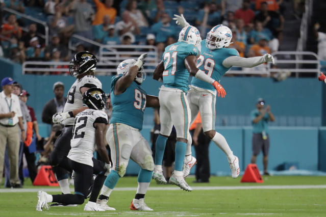 Miami Dolphins cornerback Eric Rowe (21), safety Minkah Fitzpatrick (29) and defensive tackle Christian Wilkins (97) celebrate an interception during the first half of an NFL football preseason game against the Jacksonville Jaguars, Thursday, Aug. 22, 2019, in Miami Gardens, Fla. (AP Photo/Lynne Sladky)