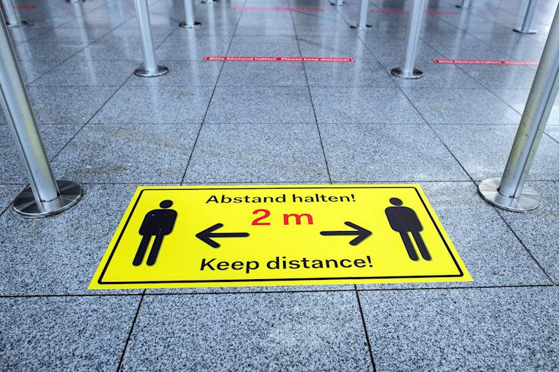 """25 March 2020, North Rhine-Westphalia, Duesseldorf: """"Keep your distance!"""" is written on stickers on the floor of the departure lounge at the airport. Air traffic is being severely disrupted by the coronavirus crisis. Photo: Federico Gambarini/dpa (Photo by Federico Gambarini/picture alliance via Getty Images)"""