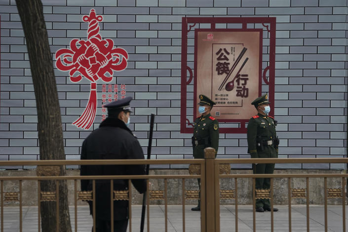 """Security personnel stand guard at a retail district near the Great Hall of the People where the opening session of the Chinese People's Political Consultative Conference (CPPCC) is held in Beijing on Thursday, March 4, 2021. The sign means """"to encourage the use of serving chopsticks for shared dishes."""" (AP Photo/Ng Han Guan)"""