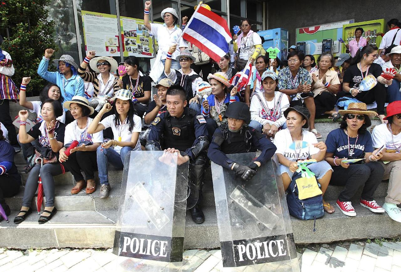Two riot police officers sit with anti-government protesters on the stairs of the National Broadcasting of Thailand (NBT) building after protesters entered the compound during a rally Friday, May 9, 2014 in Bangkok, Thailand. Thai police fired tear gas and water cannons Friday to push back hundreds of protesters trying to force their way into a government compound, the latest indication that ousting the premier will not solve the country's tense political crisis. (AP Photo/Apichart Weerawong)
