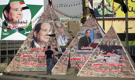 Man walks near replicas of Giza Pyramid covered with banners of presidential candidate and former army chief Abdel Fattah al-Sisi in Cairo