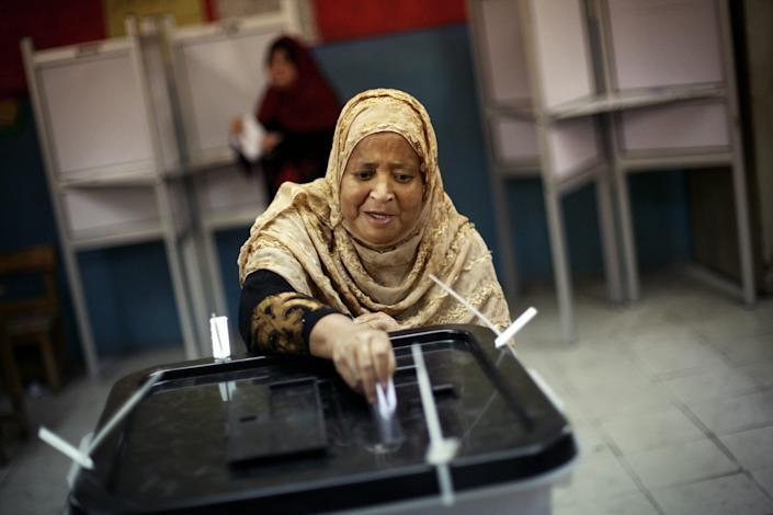 An Egyptian woman casts her vote inside a polling station in Cairo, Egypt, Thursday, May 24, 2012. In a wide-open race that will define the nation's future political course, Egyptians voted Thursday on the second day of a landmark presidential election that will produce a successor to longtime authoritarian ruler Hosni Mubarak. (AP Photo/Manu Brabo)