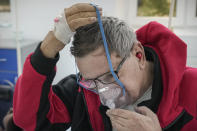Florin Sandu, 72 years-old, places an oxygen mask on his face at the COVID-19 unit of the Marius Nasta National Pneumology Institute in Bucharest, Romania, Thursday, Sept. 23, 2021. Daily new coronavirus infections in Romania, a country of 19 million, have grown exponentially over the last month, while vaccine uptake has declined to worrying lows. Government data shows that 91.5% of COVID-19 deaths in Romania between Sept. 18-23 were people who had not been vaccinated. (AP Photo/Vadim Ghirda)