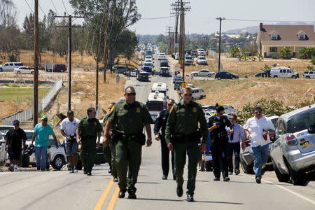 Buses packed with undocumented migrants retreat up the road after being stopped in their tracks by demonstrators in Murrieta, California July 1, 2014. REUTERS/Sam Hodgson