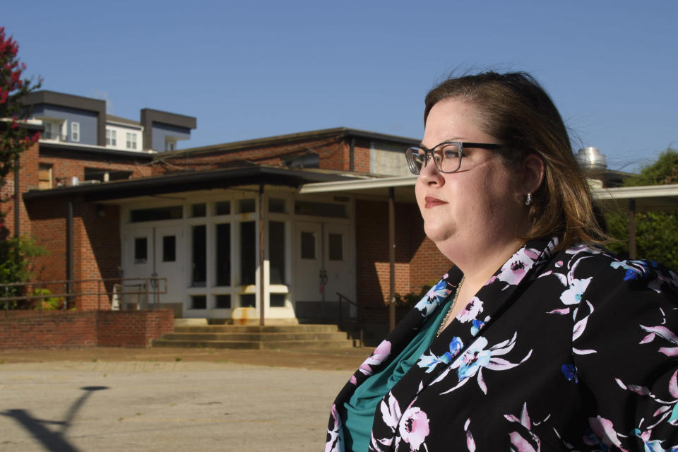 Beth Brown, Tennessee Education Association president, poses at an old elementary school property that is scheduled to be turned into the Nashville Classical II charter school, Wednesday, Aug. 11, 2021, in Nashville, Tenn. The future charter school is one that Governor Bil Lee is using federal covid aid to help launch. Brown opposes the the use of this aid to help launch new charter schools. (AP Photo/John Amis)