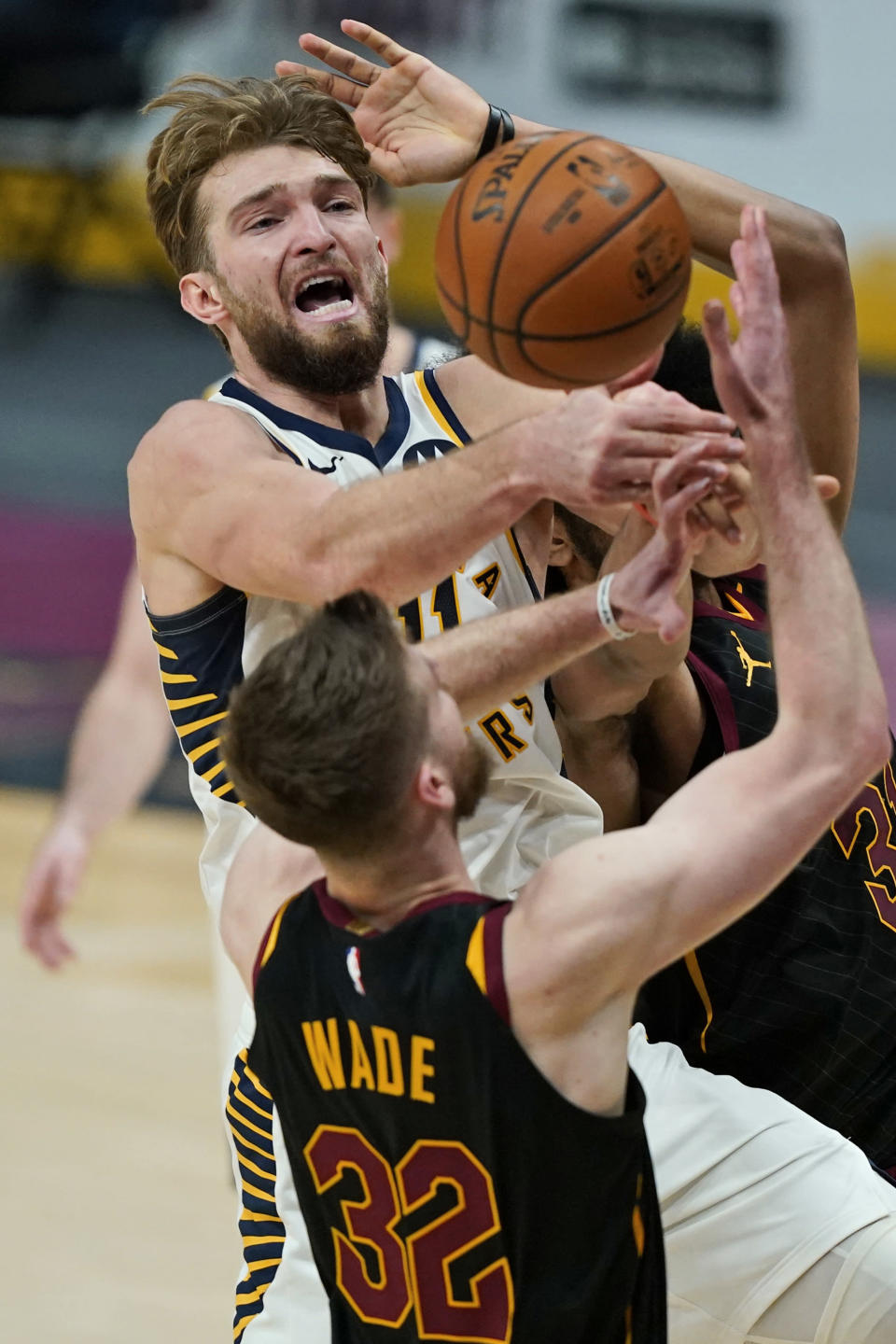 Indiana Pacers' Domantas Sabonis (11) loses control of the ball as Cleveland Cavaliers' Dean Wade (32) defends during the second half of an NBA basketball game Wednesday, March 3, 2021, in Cleveland. (AP Photo/Tony Dejak)