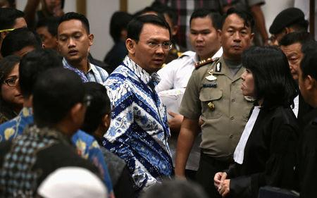 FILE PHOTO: Jakarta's Christian governor Basuki Tjahaja Purnama (L), popularly known as Ahok, speaks to his lawyers after his sentencing during the guilty verdict in his blasphemy trial in Jakarta on May 9, 2017. REUTERS/Bay Ismoyo/Pool/File Photo