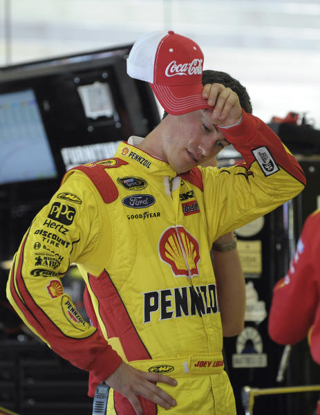 FILE - In this Aug. 30, 2013, file photo, driver Joey Logano wipes his face during a practice session for NASCAR Sprint Cup series auto race at Atlanta Motor Speedway in Hampton, Ga. Logano is the latest driver caught in the fallout of NASCAR's investigation into the field-deciding race for the Chase for the Sprint Cup championship at Richmond. (AP Photo/Dave Tulis, File)