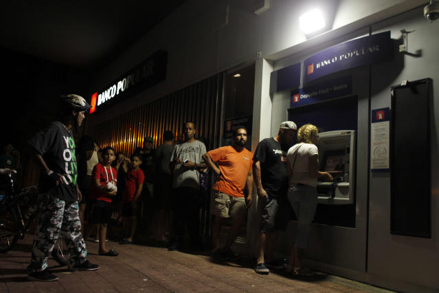 <p>People make line at night at an ATM to withdraw money in San Juan, Puerto Rico, on September 25, 2017, where a 7pm-6am curfew has been imposed following impact of Hurricane Maria on the island. (Photo: Ricardo Arduengo/AFP/Getty Images) </p>