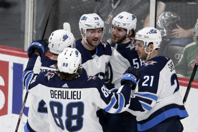 Winnipeg Jets right wing Logan Shaw (38) is congratulated by teammates Jansen Harkins (58), Nicholas Shore (21), Anthony Bitetto and Nathan Beaulieu (88) after scoring a goal on the Minnesota Wild in the third period of an NHL hockey game Saturday, Dec. 21, 2019, in St. Paul, Minn. The Jets defeated the Wild 6-0. (AP Photo/Andy Clayton-King)