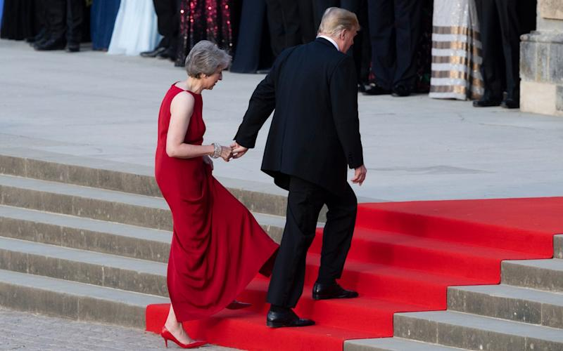 Theresa May takes the hand of President Donald Trump as they walk up red-carpeted steps to enter Blenheim Palace for a black tie dinner in Blenheim, England - PA