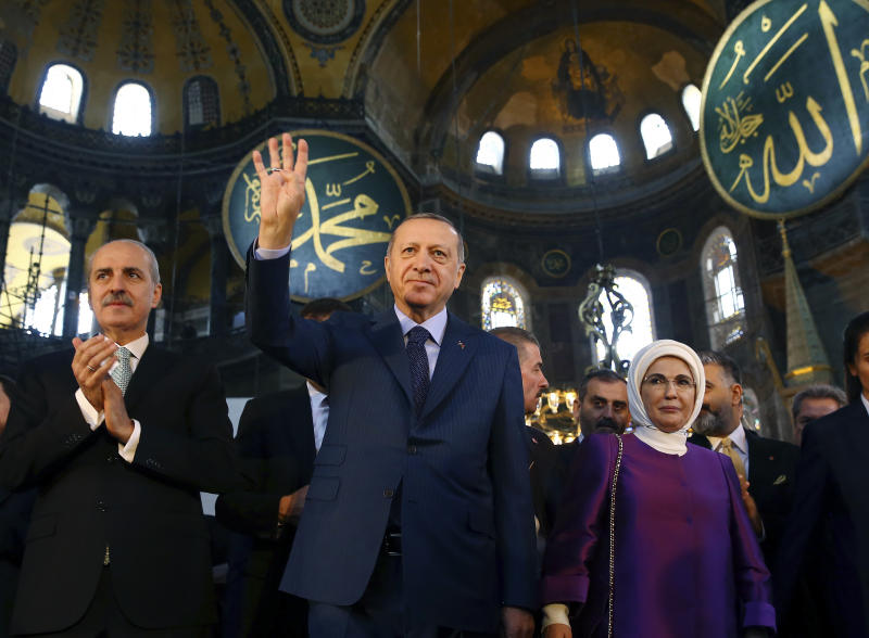 FILE - In this Saturday, March 31, 2018 file photo, Turkey's President Recep Tayyip Erdogan, centre, accompanied by his wife Emine, right, waves to supporters as he walks in the Byzantine-era Hagia Sophia, an UNESCO world heritage site and one of Istanbul's main tourist attractions, in the historic Sultanahmet district of Istanbul. The 6th-century building is now at the center of a heated debate between conservative groups who want it to be reconverted into a mosque and those who believe the World Heritage site should remain a museum. (Kayhan Ozer/Pool Photo via AP, File)